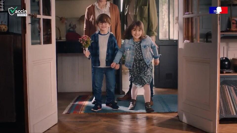 Deux enfants sourient devant leurs parents.