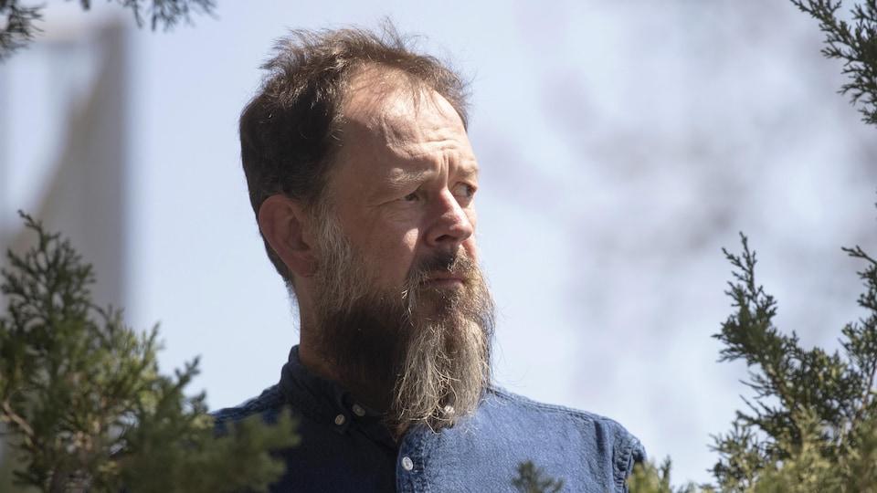 Un homme photographié à travers des branches d'arbre.