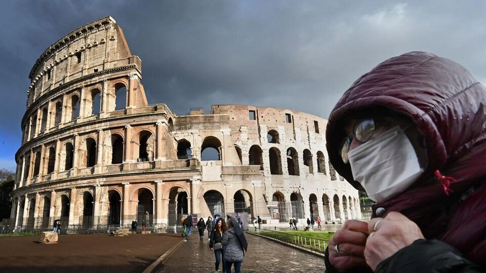 Un homme portant un masque de protection passe devant le Colisée, à Rome.
