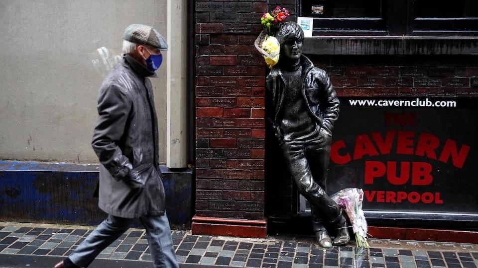 Un passant masqué marchant devant une statue de John Lennon accotée à un pub.