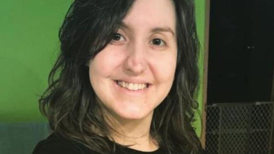 Une jeune femme au visage souriant.