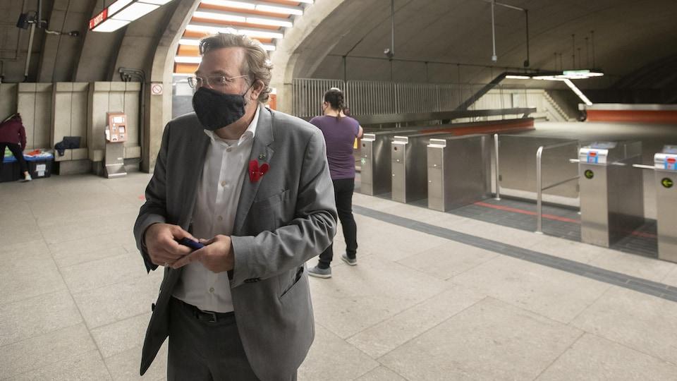 Philippe Schnobb portant un masque dans une station de métro de Montréal.