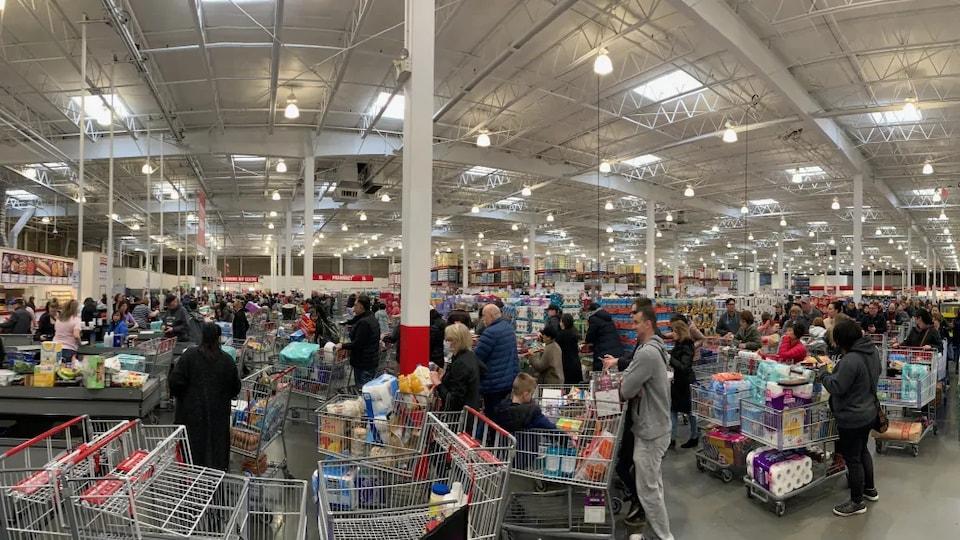 Un supermarché plein de monde avec des chariots remplis.