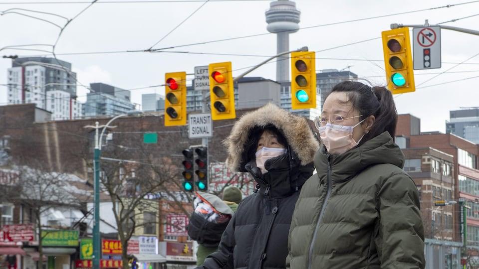 Deux femmes marchent dans le quartier chinois à Toronto en portant un masque.