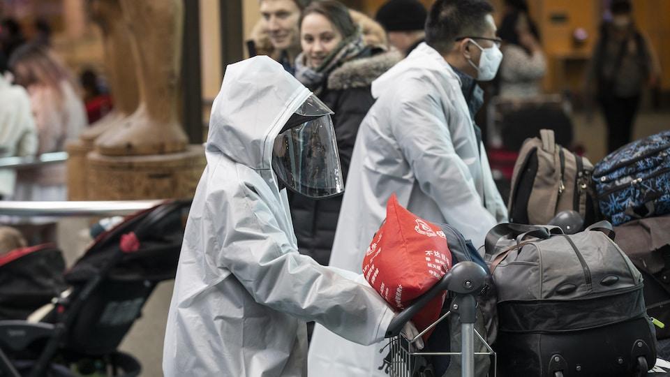 Des passagers portant un uniforme de protection complet à l'aéroport de Vancouver (YVR)