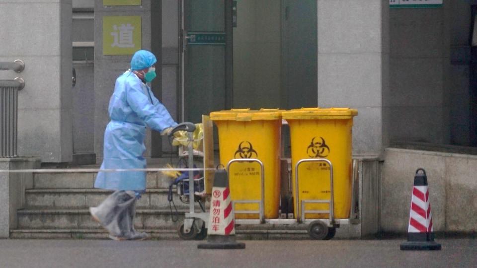 Un homme en vêtements de protection transporte des contenants de déchets biomédicaux.