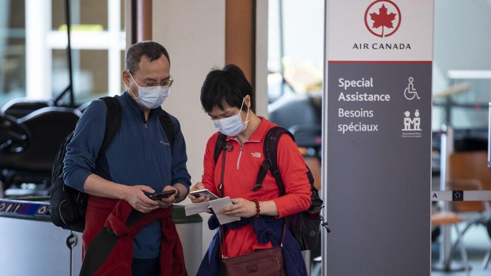 Des passagers vérifient leurs billets au kiosque d'Air Canada.