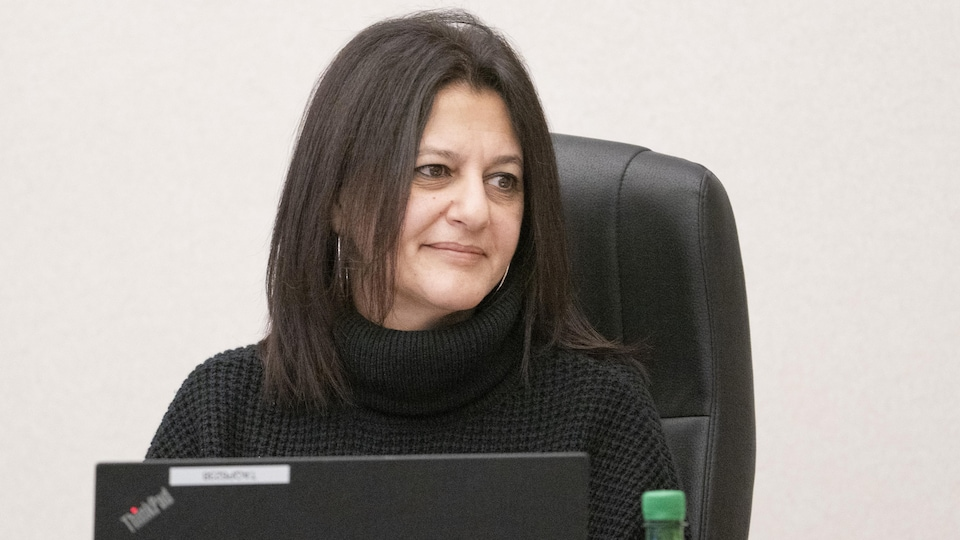 Géhane Kamel assise derrière son ordinateur.