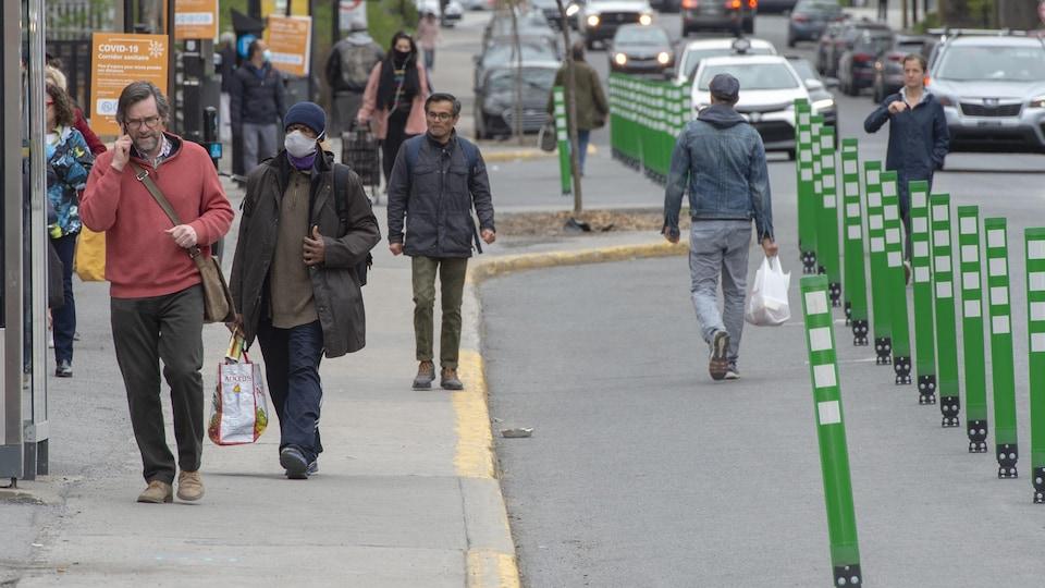 Des gens marchent sur la rue.
