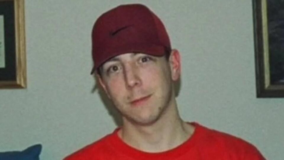 Photo d'un homme coiffé d'une casquette souriant à la caméra.