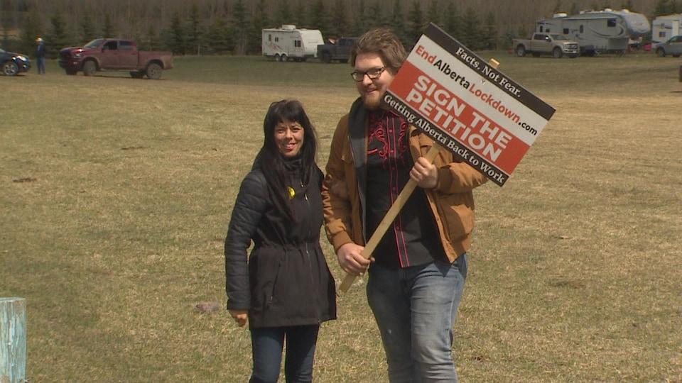 Un homme et une femme tiennent une pancarte anti-restrictions en Alberta.