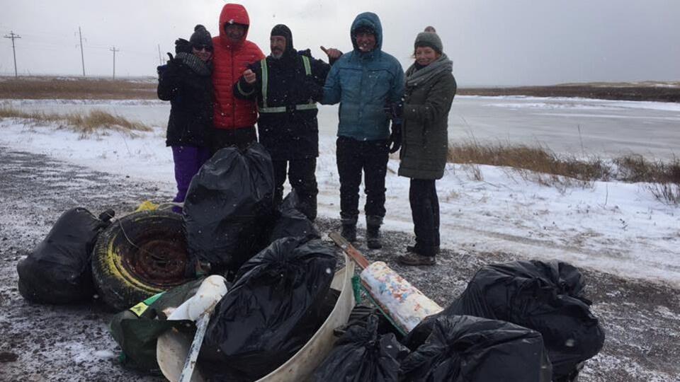 Cinq Madelinots posent fièrement devant plusieurs gros sacs de poubelle emplis de déchets.