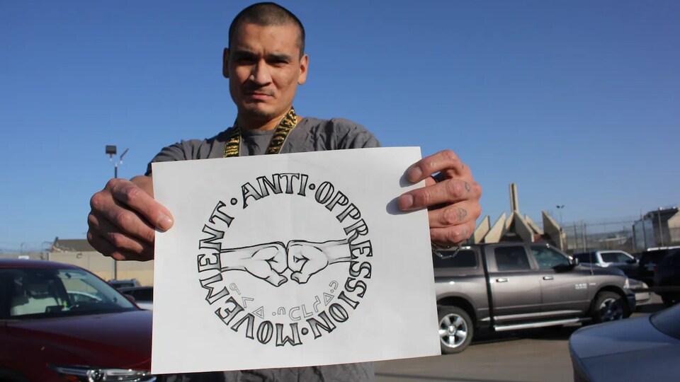 Cory Cardinal montre un dessin qu'il a créé en prison. Il représente deux points qui se touchent avec écrit en rond autour : Mouvement anti-oppression. Il tient ce dessin avec ses deux mots sur un parking.