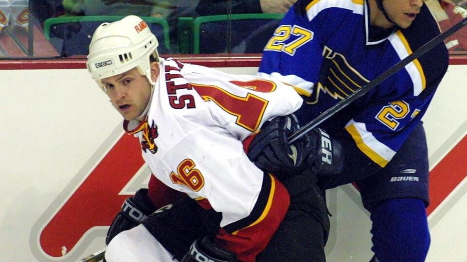Corey Stillman met un joueur en échec un adversaire durant un match de hockey.