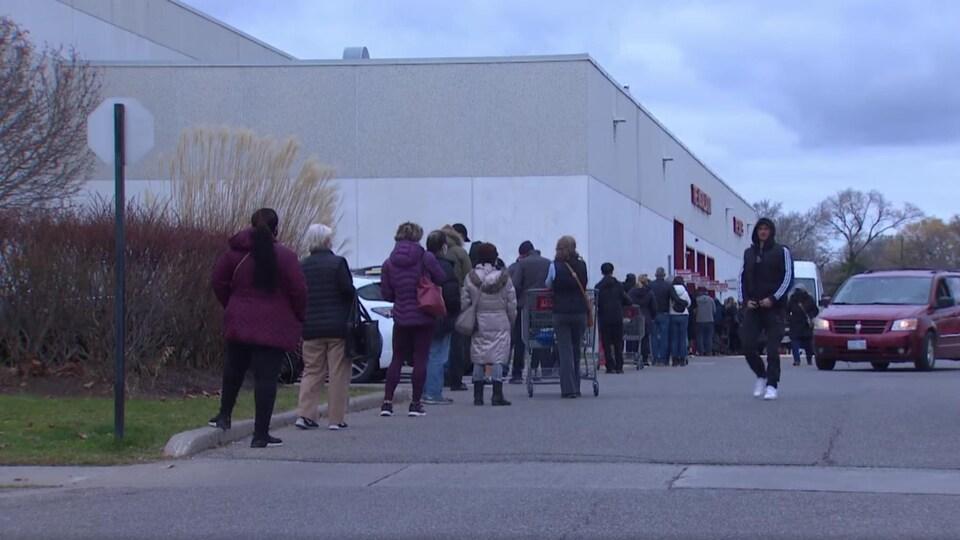 Des gens attendent pour entrer dans un magasin.