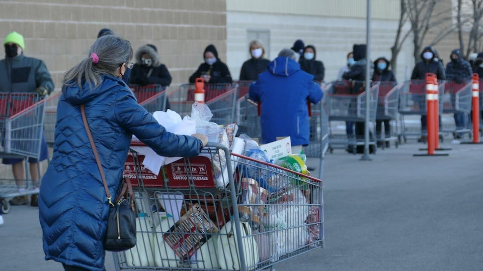 Des gens portant des masques, derrière des paniers d'épicerie vides, font la file à l'extérieur d'un commerce. Au premier plan, une femme vue de dos à la sortie du commerce pousse un panier rempli.