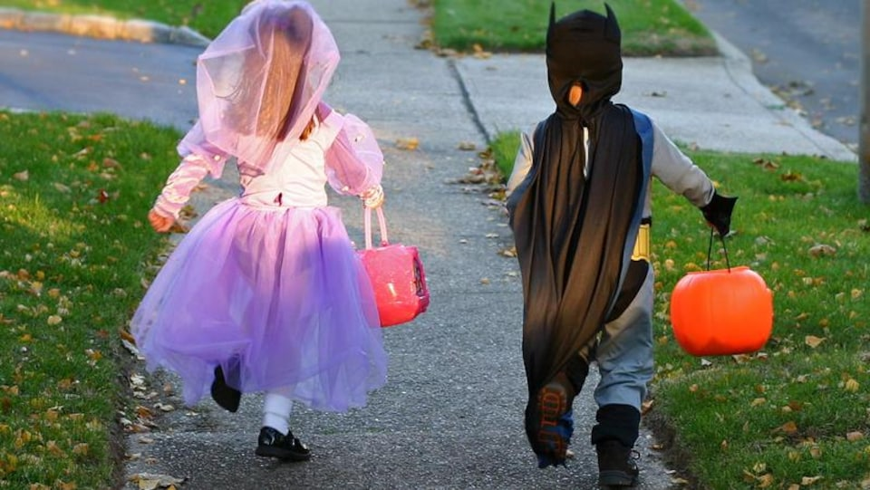 Deux enfants courent dans la rue avec des sacs pour ramasser des friandises. Ils sont déguisés pour l'Halloween.