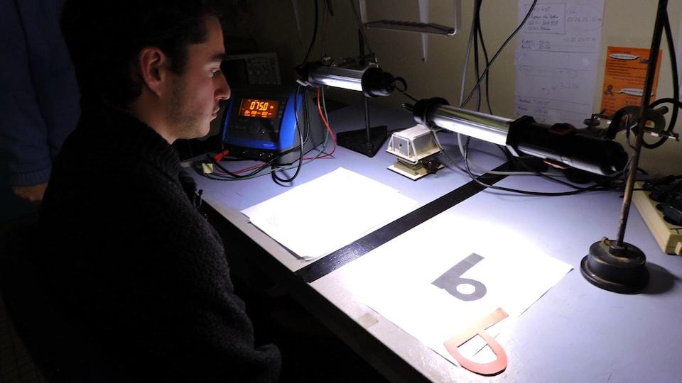 On voit Edwin Cotar en train de lire, assis, à la lumière de la lampe électrique.