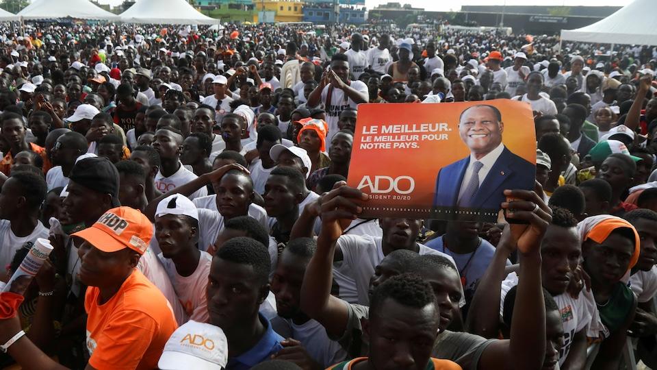 Une foule partisans arborant un portrait d'Alsane Ouattara