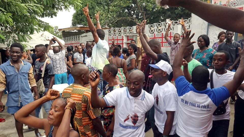 Des gens dansent et crient de joie dans la rue.