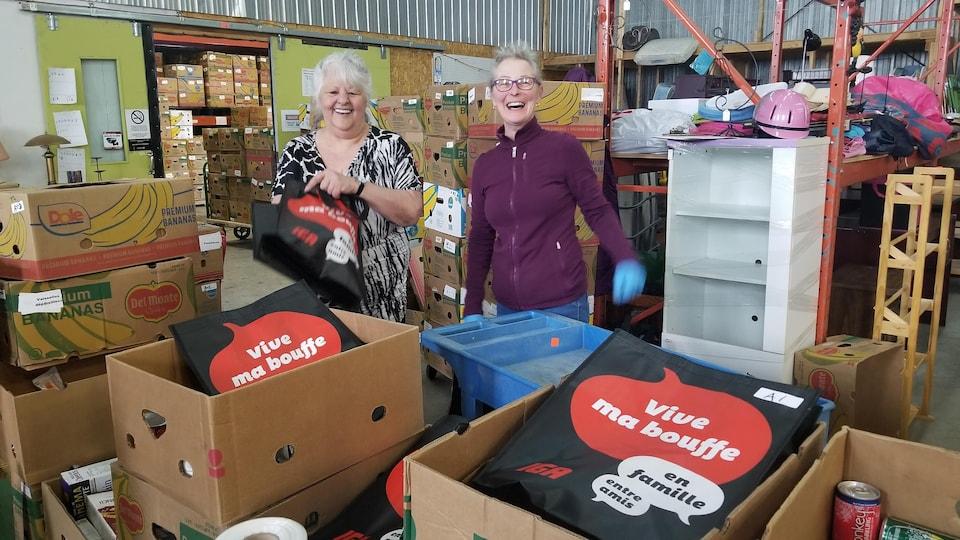 Deux femmes préparent des boîtes de nourriture dans un entrepôt, le sourire fendu jusqu'aux oreilles.