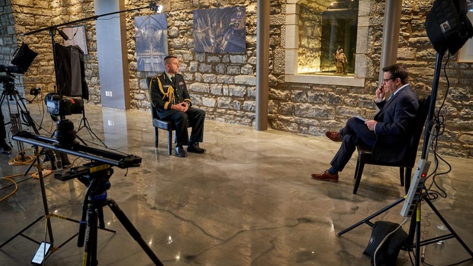 Deux hommes sont assis sur des chaises dans un décor fait de vieilles pierres. On voit le matériel nécessaire au tournage.