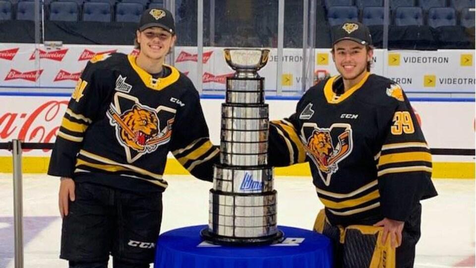 Zachaël Turgeon et Nathan Darveau ont chacun une main sur la Coupe du Président sur la glace du Centre Vidéotron de Québec.