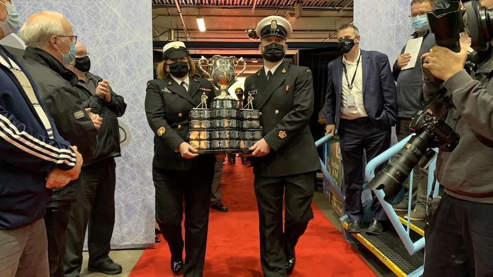 La Coupe Memorial arrive à St-Jean. Des policiers transportent la Coupe, devant une foule de gens.