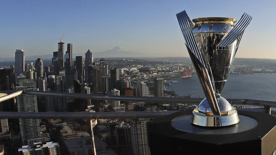 La coupe du championnat MLS présentée sur le toit d'un immeuble de Seattle avec la vue panoramique de la ville derrière.