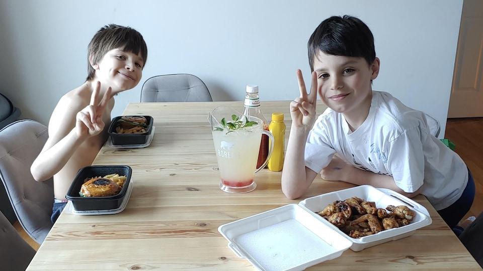 Deux jeunes garçons à table, devant leur dîner.