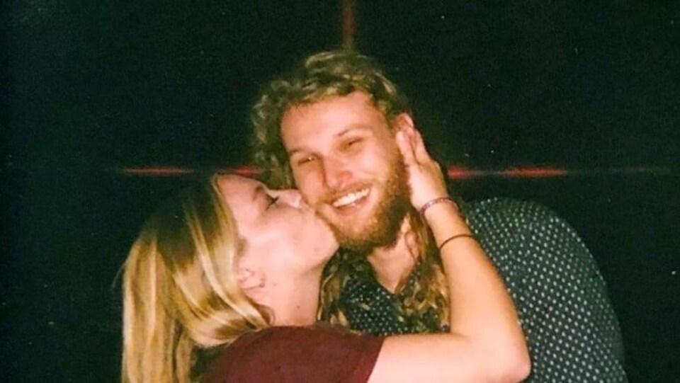 Une jeune femme blonde embrasse un homme jeune barbu aux cheveux longs.