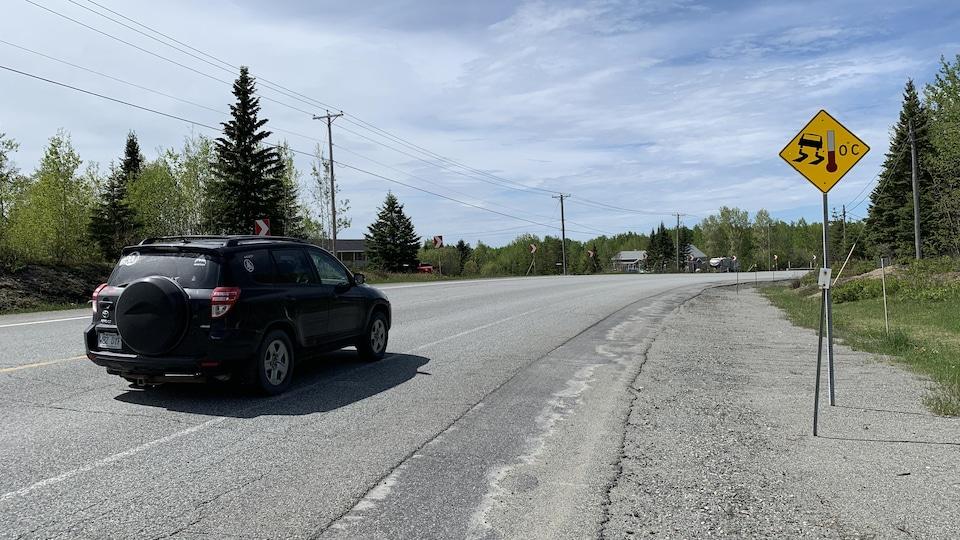 Une voiture amorce une courbe prononcée sur une route régionale.