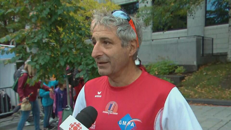 Un homme en entrevue avant le départ du marathon de Québec
