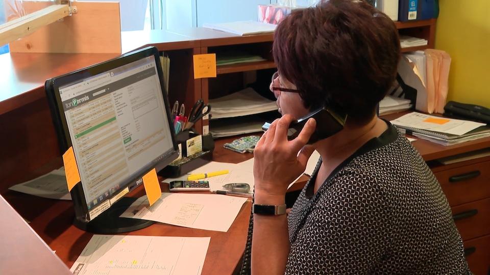 Une femme répond au téléphone.
