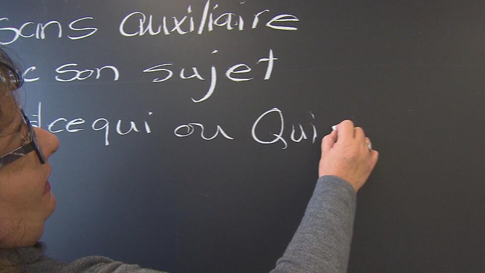 Une femme explique la grammaire française en écrivant sur une ardoise à l'aide d'une craie.