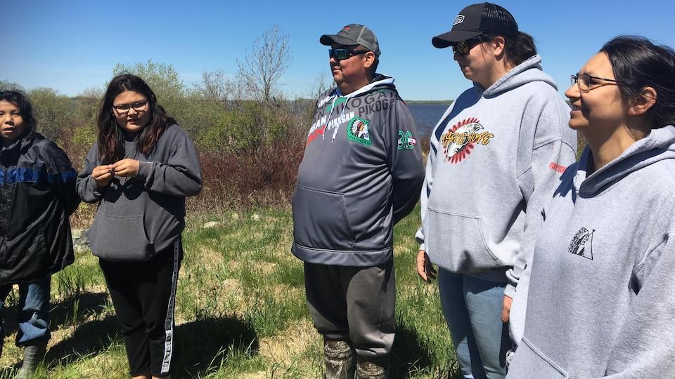 Quatre femmes et un homme d'origine autochtone écoutent une personne hors-champ.