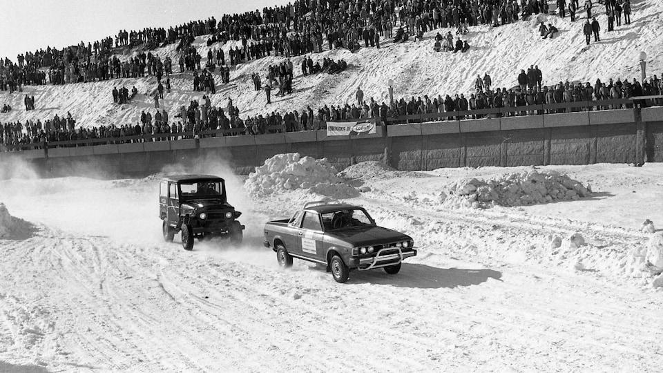 Un jeep tente un dépassement sur la piste enneigée de la rivière Saint-Charles  sous le regard attentif de la foule massée sur les berges bétonnées de la Saint-Charles.