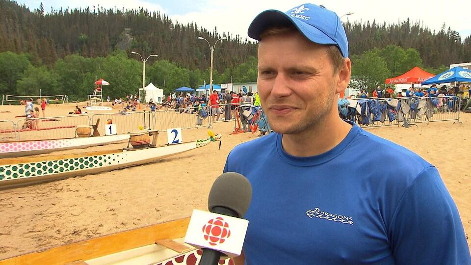 Il accorde une entrevue sur la plage près d'un bateau.