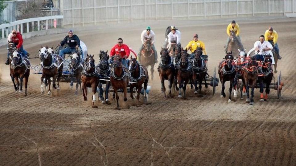 Quatre chariots chacun tiré par quatre chevaux côte à côte sur la piste de course.