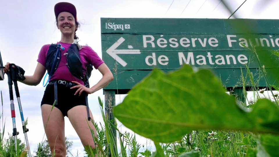 Charlotte Levasseur Paquin pose avec ses bâtons de marche devant une pancarte de la Sépaq.