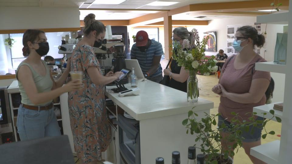 Une personne apporte un café à une cliente au comptoir.