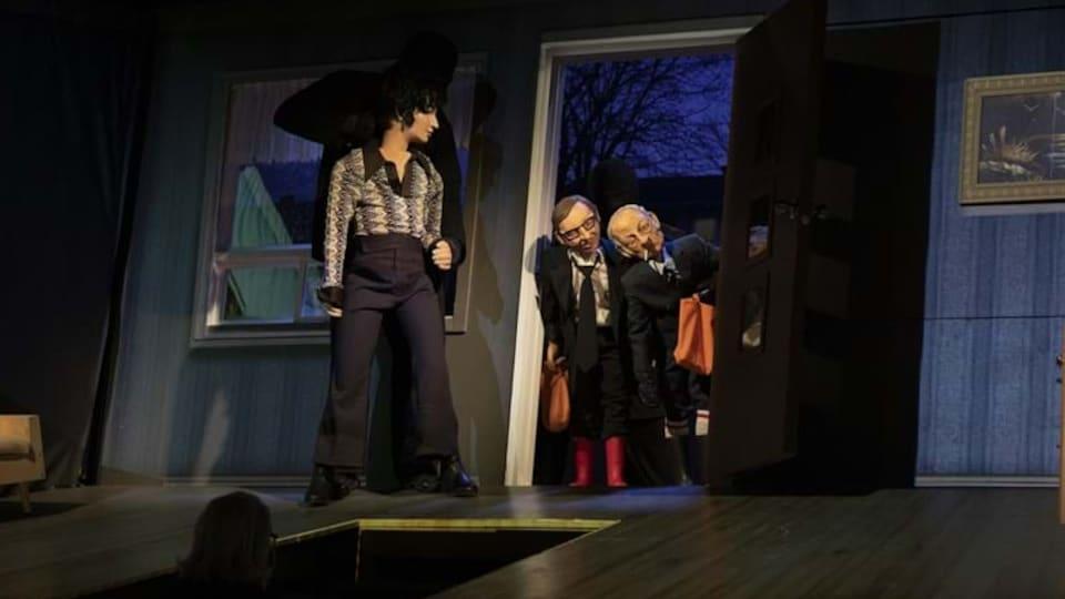 Trois marionnettes sur une scène, dont une femme et deux hommes dans un cadre de porte, représentant René Lévesque et Robert Bourassa.