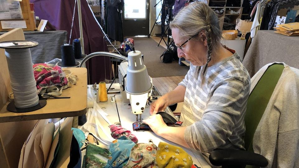 Une couturière derrière sa machine à coudre en train de confectionner des masques non médicaux.