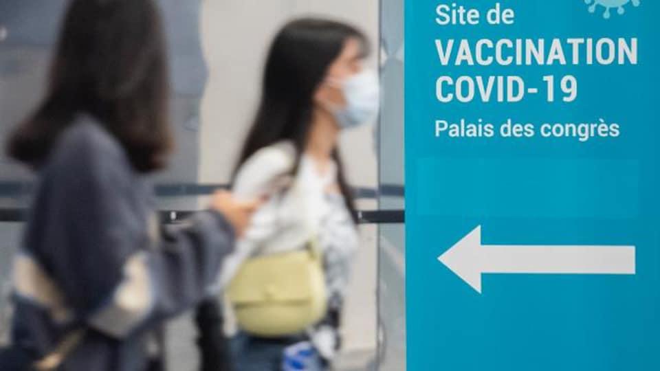Des personnes portant un masque marchent vers un centre de vaccination.