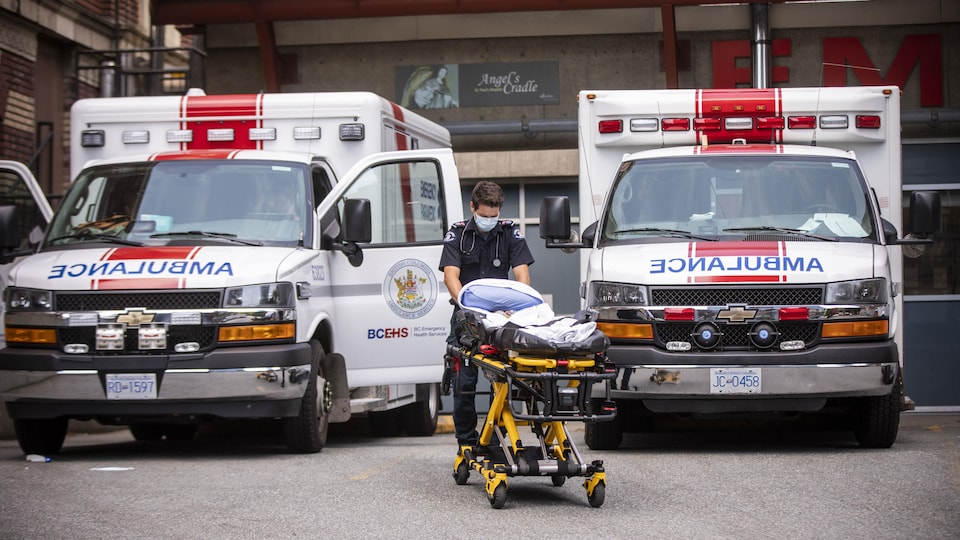 Un ambulancier pousse une civière entre deux ambulances à l'hôpital St-Paul de Vancouver.