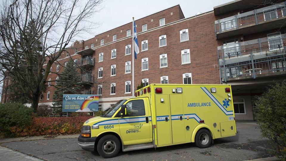 Une ambulance passe devant le CHSLD et une pancarte sur laquelle on peut lire : « Ça va bien aller ».