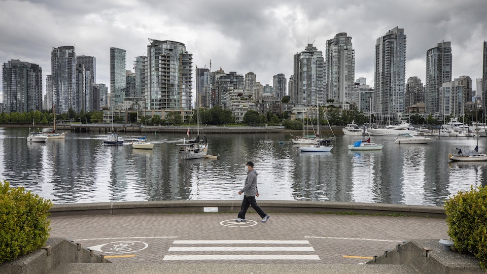 Un homme marche le long du Seawall de False Creek, à Vancouver.