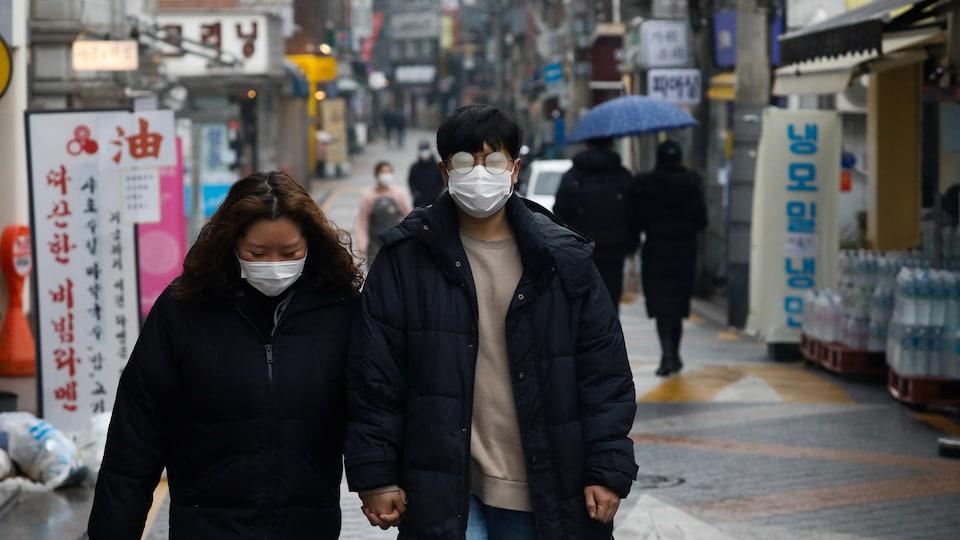 Un couple portant des masques chirurgicaux marche dans une rue.