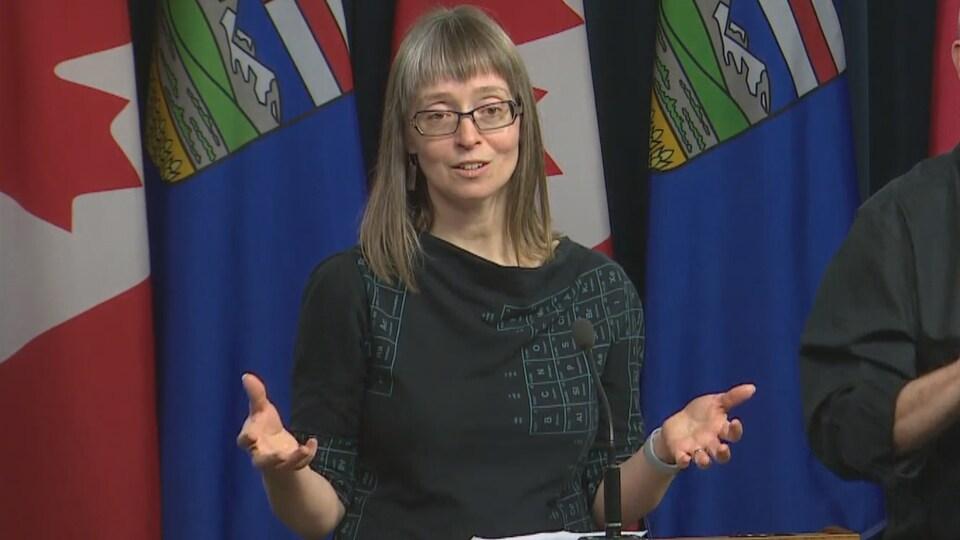 La médecin hygiéniste en chef de l'Alberta, Deena Hinshaw, porte une robe noire dont l'imprimé reprend le tableau périodique des éléments.