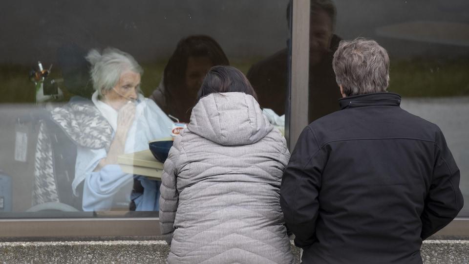Des visiteurs regardent une patiente par la fenêtre du CHSLD Éloria-Lepage à Montréal.